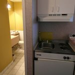 Kitchenette with plates, stovetop, sink, microwave and mini-fridge.