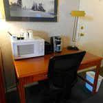 Kitchenette room's desk with microwave and coffee machine (sink, fridge and stove on opposite wa
