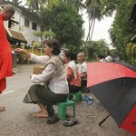 Hotel owner and neighbour ladies giving food to the monks