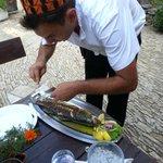 Waiter preparing our fish