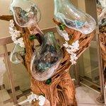 Un arredo particolare:  un tronco di legno con bottiglie di vetro adattate a caldo