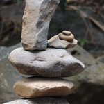 rock sculptures dot the dry river bed on the edge of the garden.