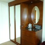 Big wardrobe with ironing board and trouser press, kettle, hairdryer, glasses and ice bucket.