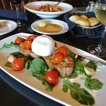 HOUSE MADE BURRATA - A creamy mozzarella from Puglia, with poached tomatoes, basil, roasted garl