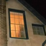image of woman with hooded cape in Fay's upstairs bedroom window (zoomed in)