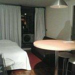 Sala com cama extra e sofá. Entrada do quarto de casal à direita