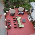 looking down from the balcony to the outdoor patio with fire pit