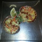 Scallops & Prawns served in a Scallop Shell With Wilted Spinach, Crispy Bacon, White Wine Sauce