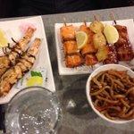 Brochettes de gambas, thon et saumon servi avec des nouilles sautées