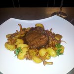 Steak with browned potatoes, jui and wild mushrooms.