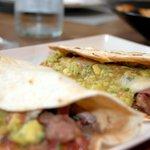 Tacos de entrecot envueltas en tortitas de harina con queso fundido, guacamole y pico de gallo.