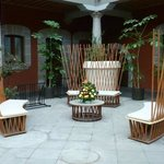 un mobiliario muy original en un patio antiguo alrededor del cual estan las habitaciones