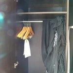 wardrobe in room w/ hangers, ironing board + iron