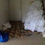 dirty bedsheet thrown on floor at corridor/walkway for guest towards room, ugly sight