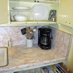 Kitchens stocked with dishes, utinsils, pots, coffee maker