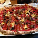 Red sauce pizza with mozzarella, meatball, mushroom, black olives, artichoke hearts and pepperon