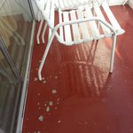 Dirty balcony, plastic chairs and worn floor tiles.