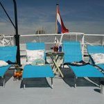 Sundeck with comfortable sunbeds and covers around for ultimate privacy