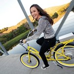A young woman on a bright yellow Pedego electric bike, touring the central California area