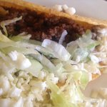 Beef buried in taco by overflowing lettuce and cheese