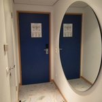 Огромное круглое зеркало напротив ванной комнаты