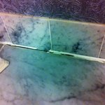 Cracked grout all along shelf in bathroom.