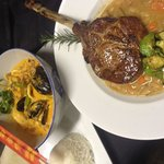 Red Duroc tomahawk chop with Tuscan beans and mixed seafood Thai red curry