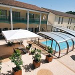 Vue sur la piscine et la terrasse de l'hôtel.