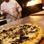 Porto's artisan pizzas are flame-roasted in Porto's copper-clad pizza oven.