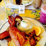 Blueberry pancakes. Poached eggs with bacon, grilled potatoes and sourdough bread. Berry smoothi