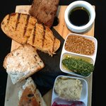 Breadboard with a trio of dips, balsamic and olive oil and dukkah