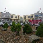 Das Hotel von aussen mit dem Haupteingang in der Mitte und dem Parkplatz davor.