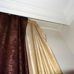 Curtains hanging off wall in bedroom