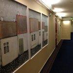 廊下。同一と思われる作者の意味不明の絵画がならぶ。まとめ買いしたのかな?