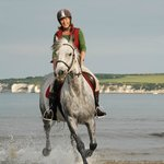 Helen riding Hattie on Studland Beach.