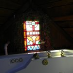 jacuzzi tub with pretty stained glass behind it