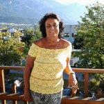 Eu na varanda com vista para a beleza dos Alpes