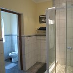 Large shower and toilet with it's own door.