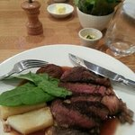 Rump steak served with greens and square cut roast potato