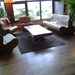 Ambiente do estar com poltrona e sofá esculpidos em troncos de árvores nativas.