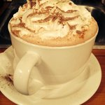 A decadent bowl of hot chocolate made with real chocolate and milk, topped with whipped cream. M