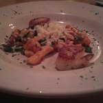 Fresh Maine diver scallops grilled and served over potato gnocchi And spinach In a fresh tomato
