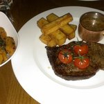Ribeye steak with duck fat chips, a side of peppercorn sauce and a side dish of roasted pumpkin.