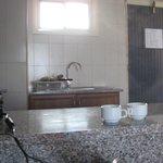 мини кухня: раковина, плита, духовка, шкафы с посудой, тостер, чайник