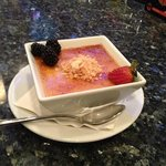 Strawberry and blackberries in a vat of coconut creme brûlée, sprinkled with toasted coconut