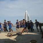 School boys jogging in the sand with the pier as a backdrop!