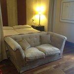 cama con dosel y sofá a los pies