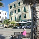 Sitting on bench in front of Hotel Miramare & Restraunt