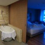 la salle de bain separee de la chambre par une cloison ouvrante