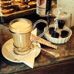 """Il """"bancone"""" dove sono stata servita. Cappuccino in primo piano e pasteis sullo sfondo."""